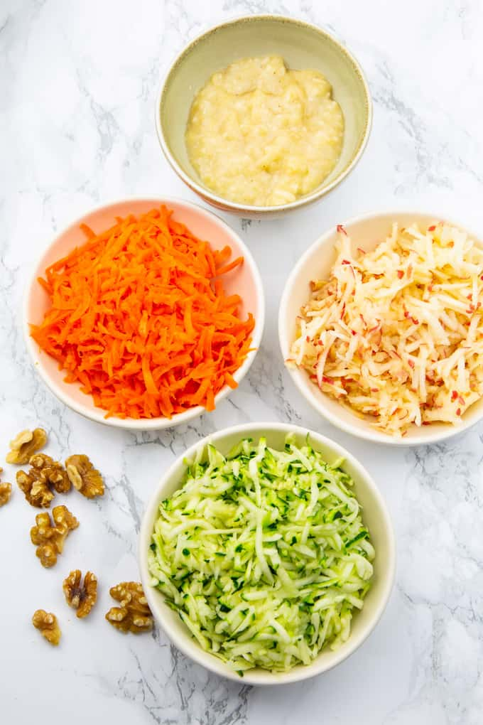 four bowls of grated zucchini, grated carrots, grated apple, and mashed banana on a marble countertop