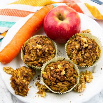 three zucchini carrot muffins on a white plate with an apple and a carrot on a marble countertop