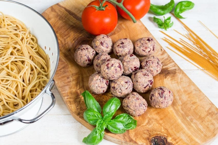 uncooked vegan meatballs on a wooden board with cooked spaghetti in a colander