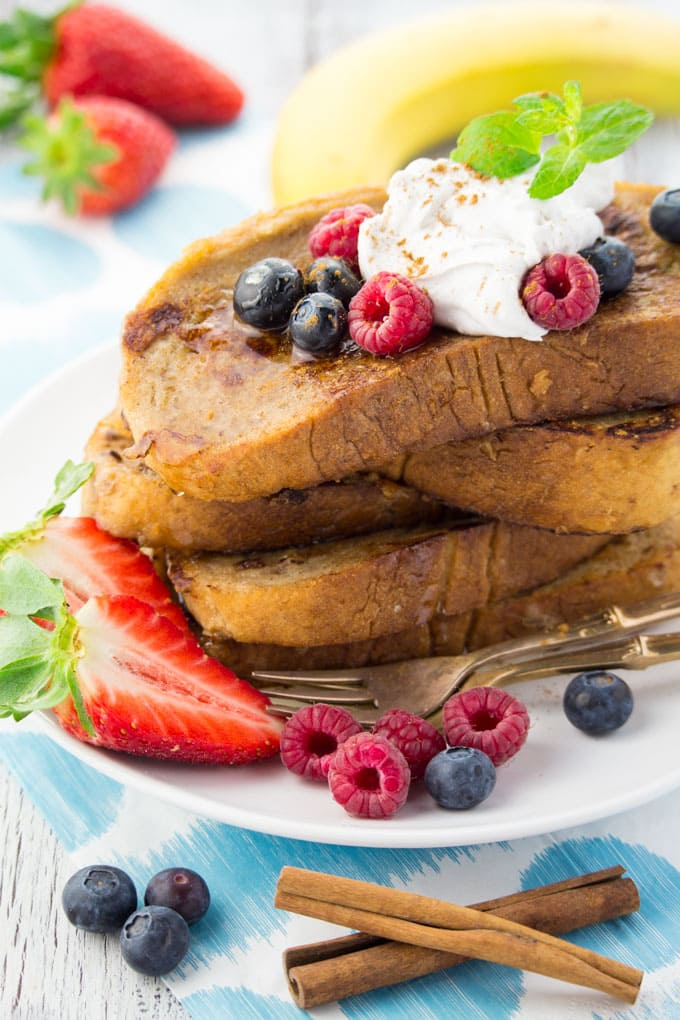 a stack of vegan French toast coconut whip cream and berries on top on a white plate with a blue napkin