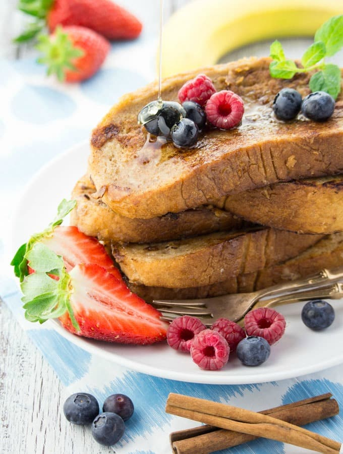 a stack of vegan French toast in a white plate with raspberries, blueberries, and strawberries on top and on the side and a banana in the background