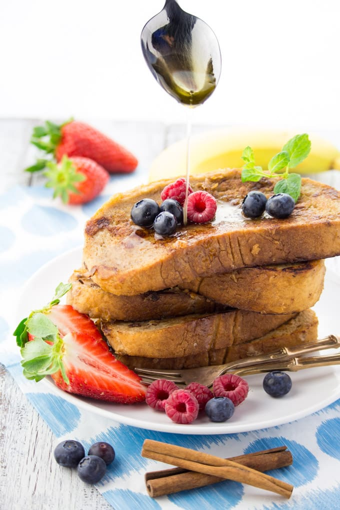 a stack of vegan French toast on a white plate with a spoon drizzling maple syrup over the French toast
