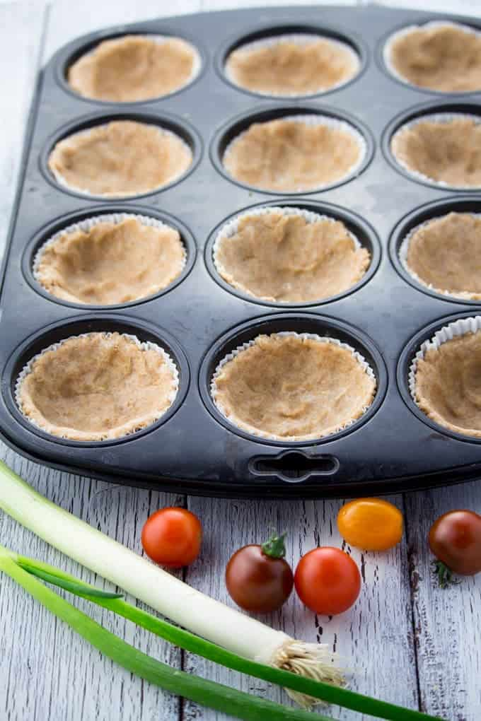 vegan quiche crust in a muffin tray before baking on a white wooden counter top with cherry tomatoes and green onions on the side