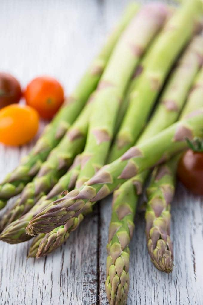 a bunch of green asparagus on a white wooden counter top with three cherry tomatoes in the background
