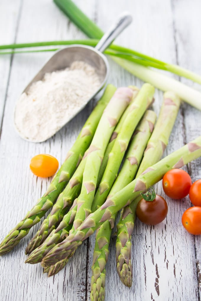 a bunch of green asparagus on a white wooden countertop with flour, green onions, and cherry tomatoes on the side and in the background