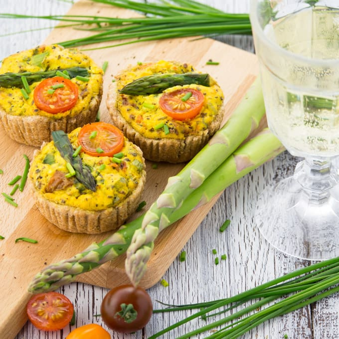 Three Vegan Quiche with asparagus on a wooden board with green asparagus, chives, tomatoes, and a glass of white wine on the side