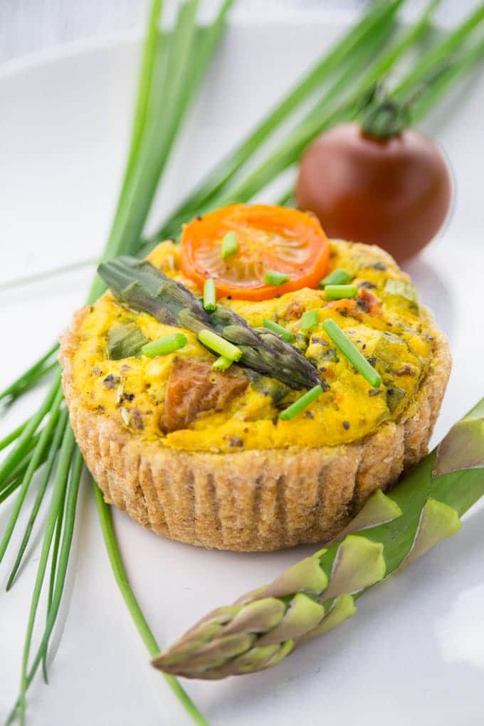 a vegan mini quiche on a white plate with chives, green asparagus, and a cherry tomato on the side