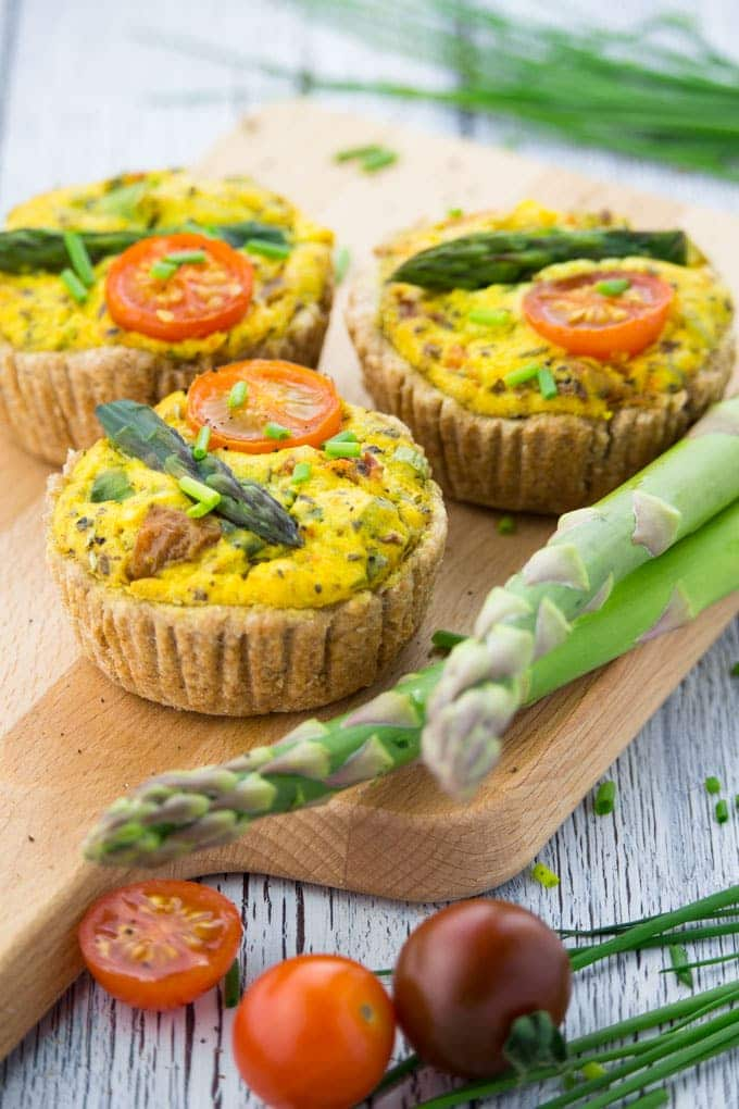 Three mini vegan quiche on a wooden board with asparagus, cherry tomatoes, and chives on the side