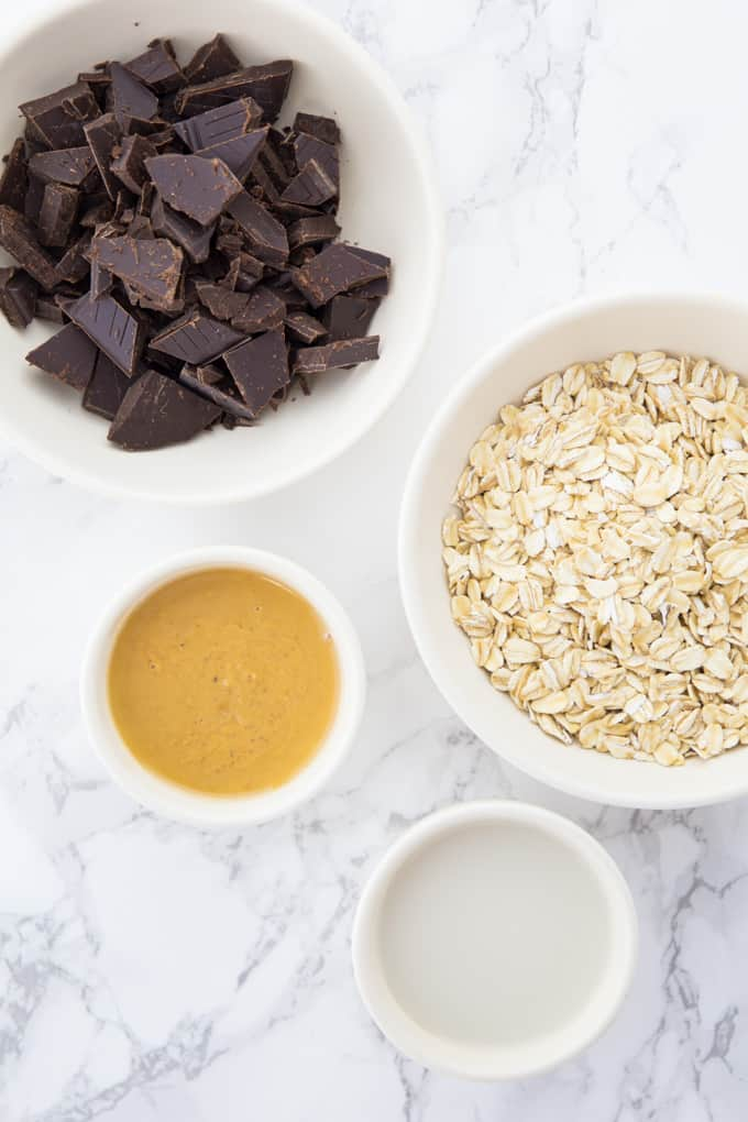 peanut butter, chopped chocolate, almond milk, and rolled oats each in little bowls on a marble counter top