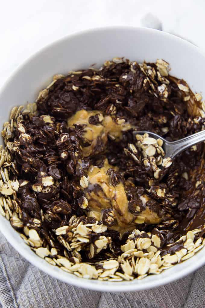 A bowl of melted chocolate with oats and peanut butter with a spoon