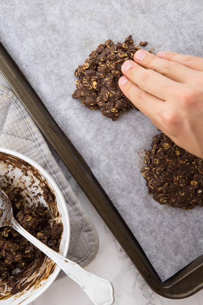 a hand forming no bake oatmeal cookies on a baking sheet lined with parchment paper