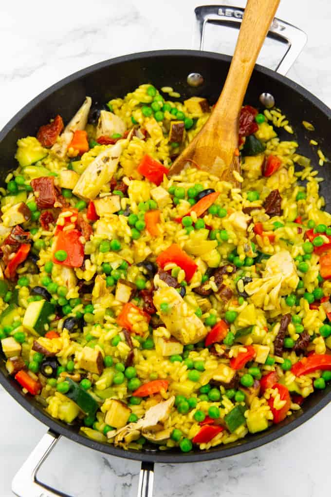Vegan Paella in a black pan with a wooden spoon on a marble countertop