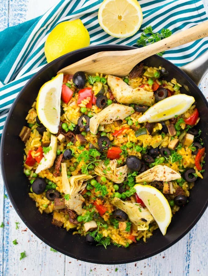 Vegan Paella in a black pan with a wooden spoon on a white and blue wooden countertop with two lemons in the background