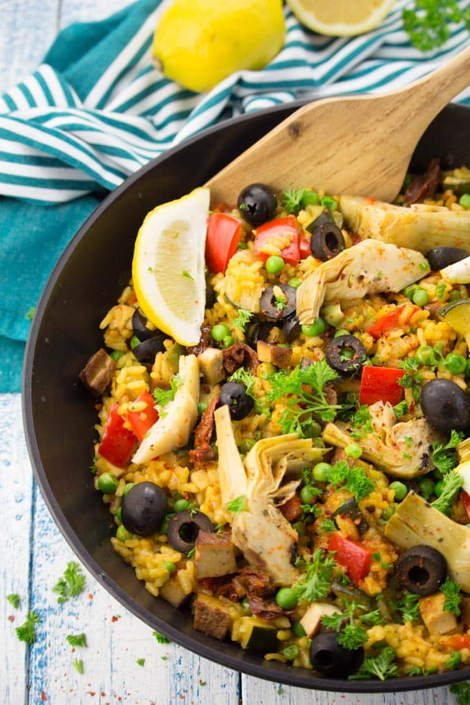 Vegan Paella in a black pan with a wooden spoon on a white and blue wooden countertop