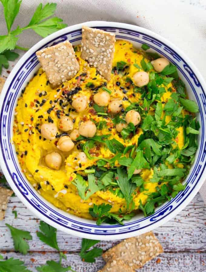 pumpkin hummus with fresh parsley, sesame seeds, and red pepper flakes on top in a blue and white bowl with sesame crackers on the side