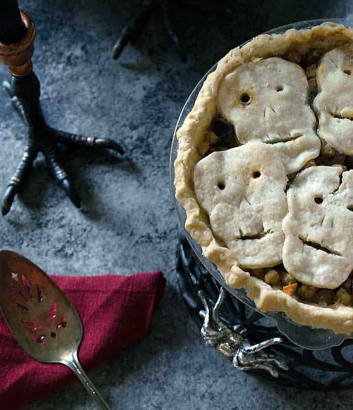 a vegan pot pie with a crust of little skulls on a grey counter top with a red napkin and a spoon on the side