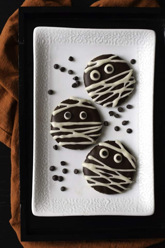 Three mummy cookies on a white plate on a dark surface with an orange dish cloth