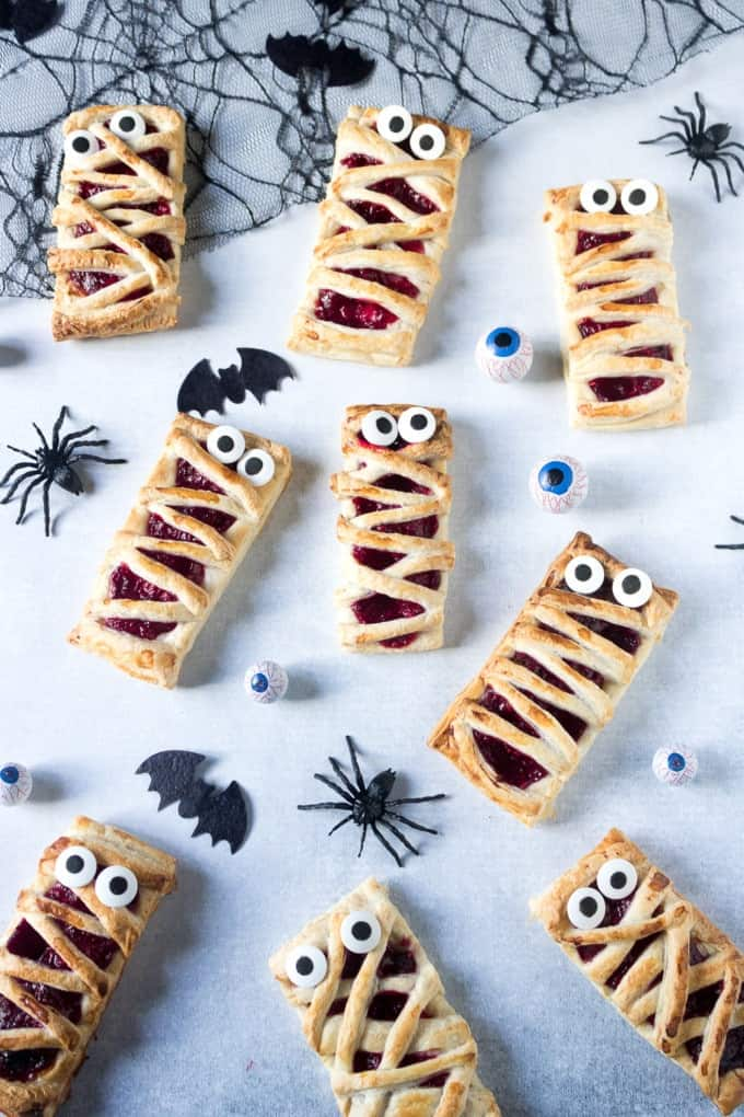 raspberry mummy pies on a white surface with plastic spiders and bats