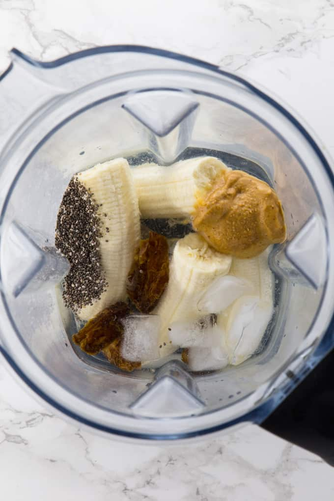 Ingredients for a banana smoothie without milk in a blender (bananas, dates, chia seeds, water, and ice cubes)