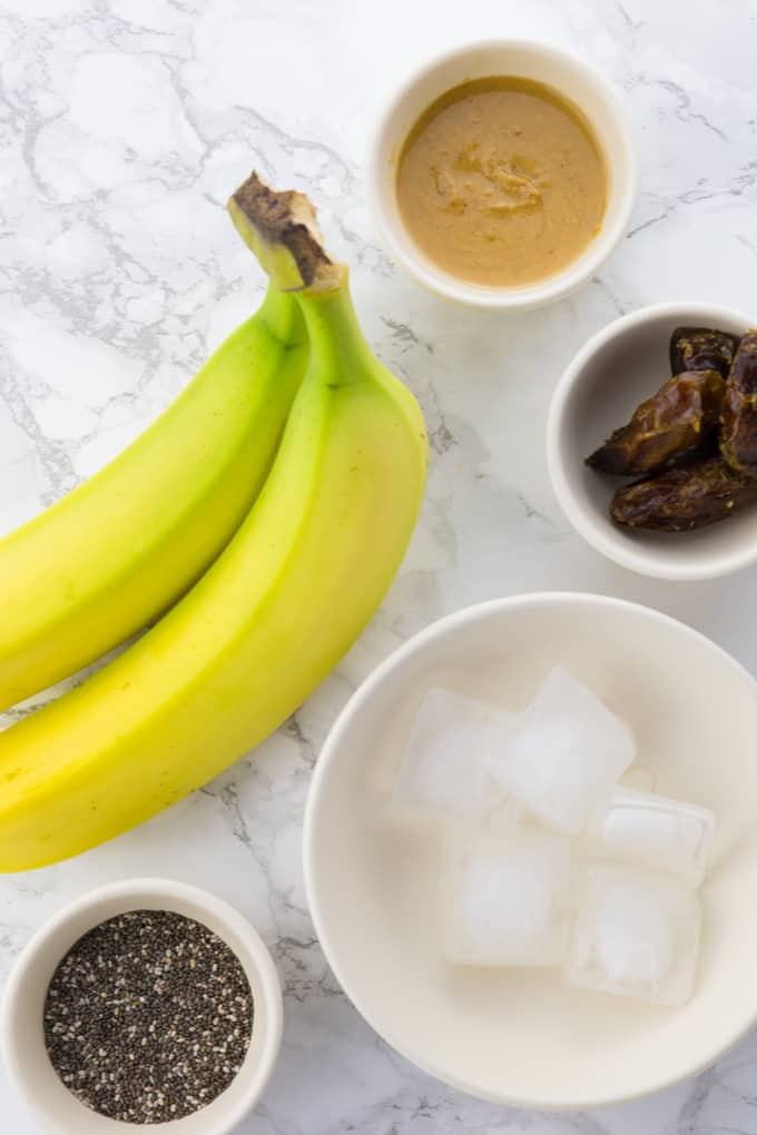 bananas, chia seeds, peanut butter, dates, and ice cubes on a marble counter top