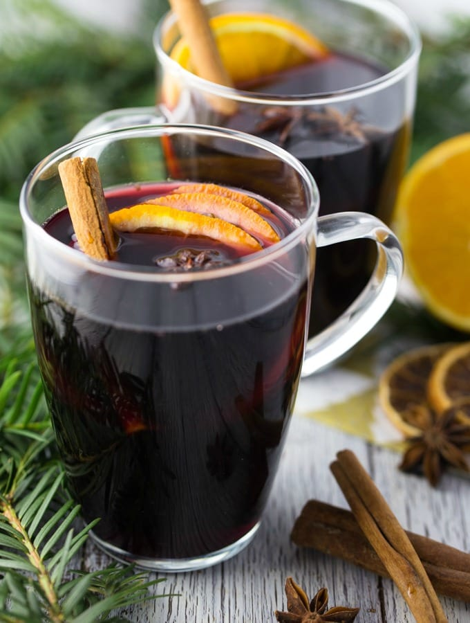 two glass mugs with mulled wine with orange slices, star anise and cinnamon sticks with fir branches on the side