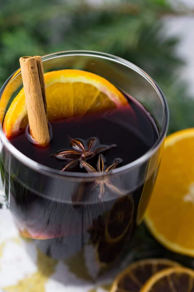a glass of mulled wine with orange slices, a cinnamon stick, and star anise with fir branches in the background