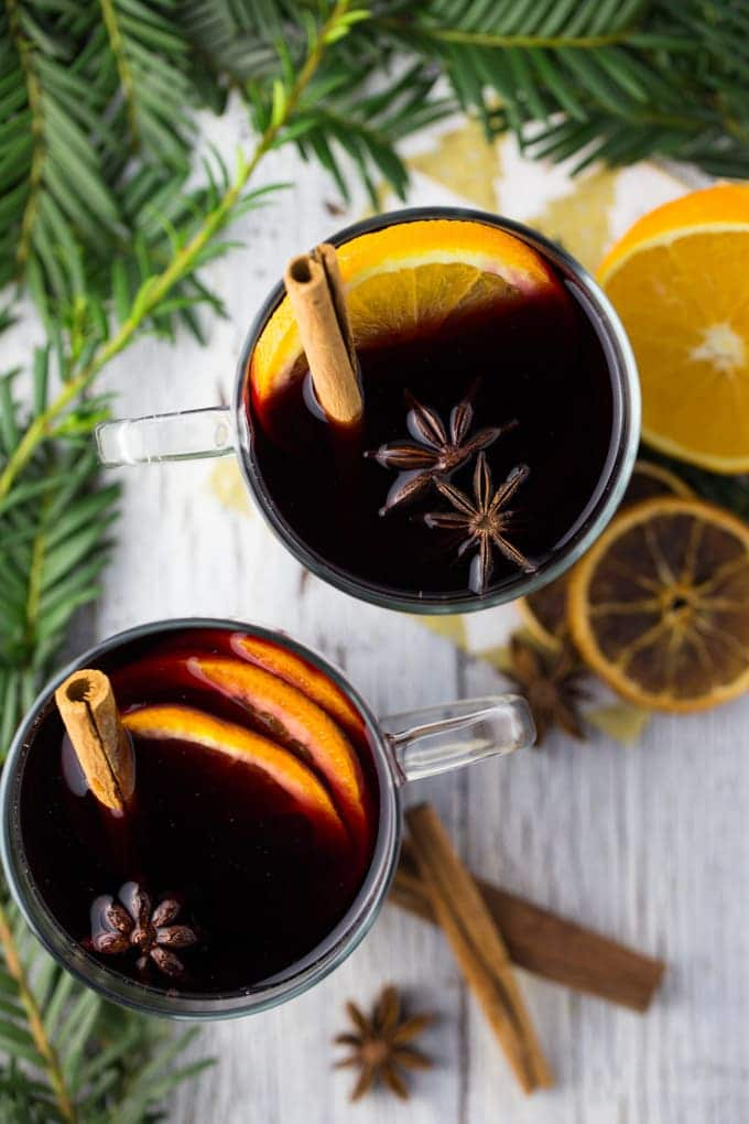 overhead shot of two glass mugs with mulled wine with orange slices, star anise and cinnamon sticks with fir branches and dried and fresh orange slices on the side