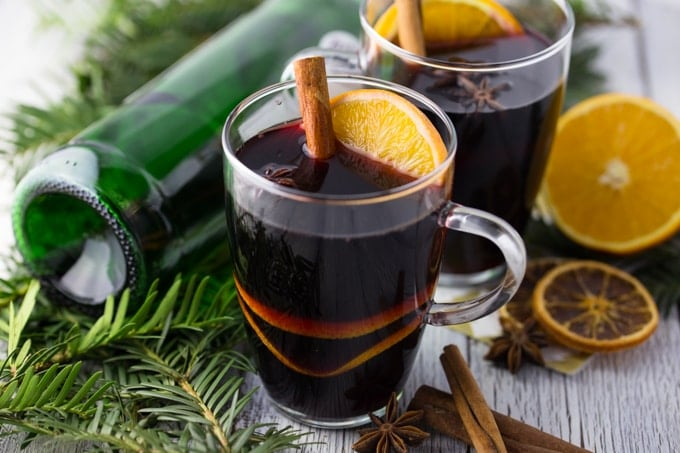 two glasses of mulled wine with a green bottle of wine, fir branches, and orange slices in the background