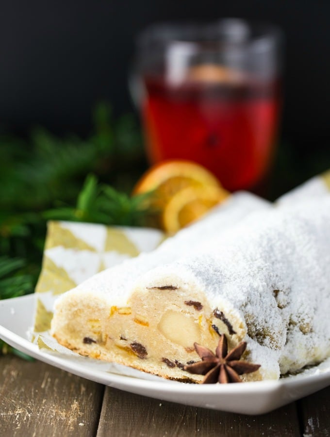 a German stollen with marzipan on a white plate with a glass of mulled wine, dried orange slices, and evergreens in the background