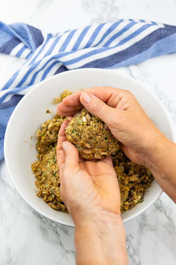 two hands forming a mushroom burger patty over a white bowl with more of the burger mixture