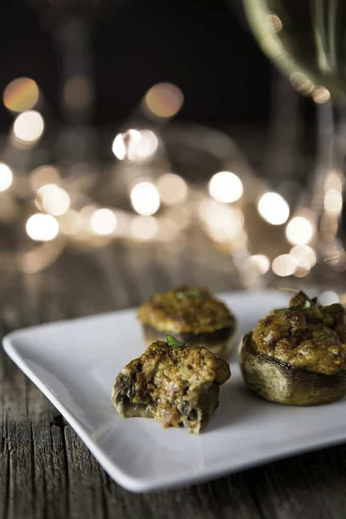 Three vegan stuffed mushrooms on a white plate with lights in the background
