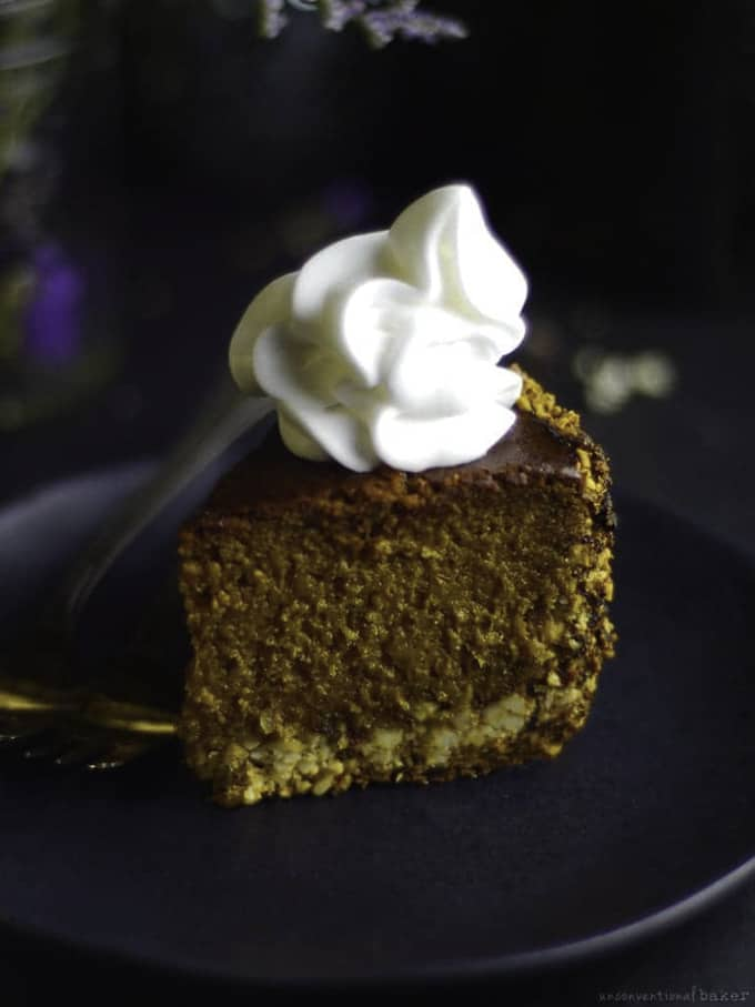 a piece of baked pumpkin cheesecake with coconut whip on top on a black plate with black background