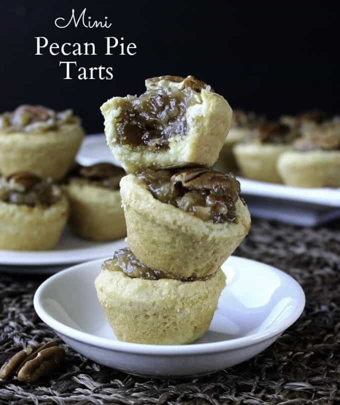 a stack of three vegan mini pecan pie tarts on a white plate with more tarts in the background