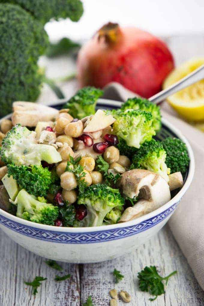 veggie salad with broccoli, mushrooms, and pomegranate in a blue and white bowl with broccoli, a whole pomegranate, and a lemon in the background