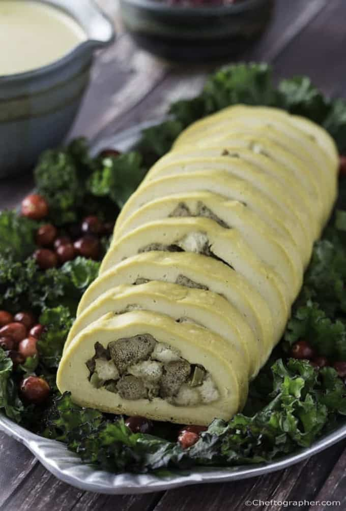 vegan turkey roll on a bed of kale and cranberries with gravy in the background