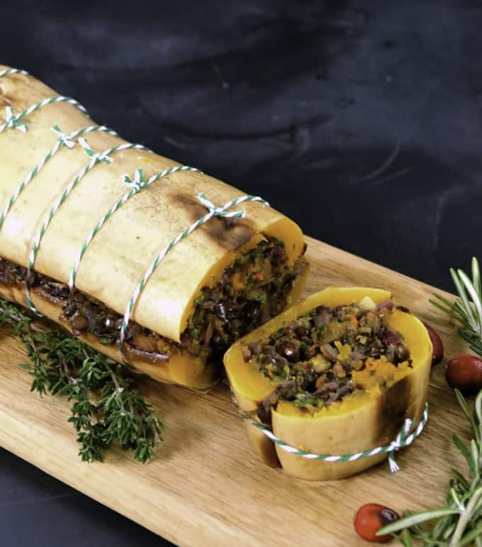 butternut roast on a wooden board with fresh herbs on the side