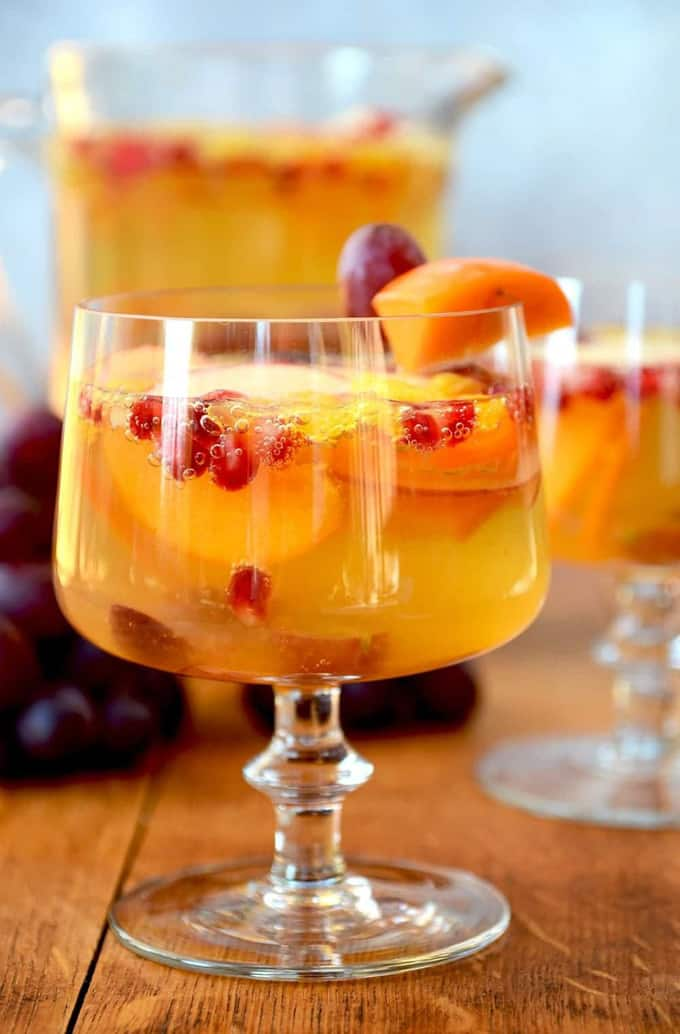 a glass of cider sangria with grapes, persimmons, and oranges on a wooden board with a pitcher of more sangria in the background