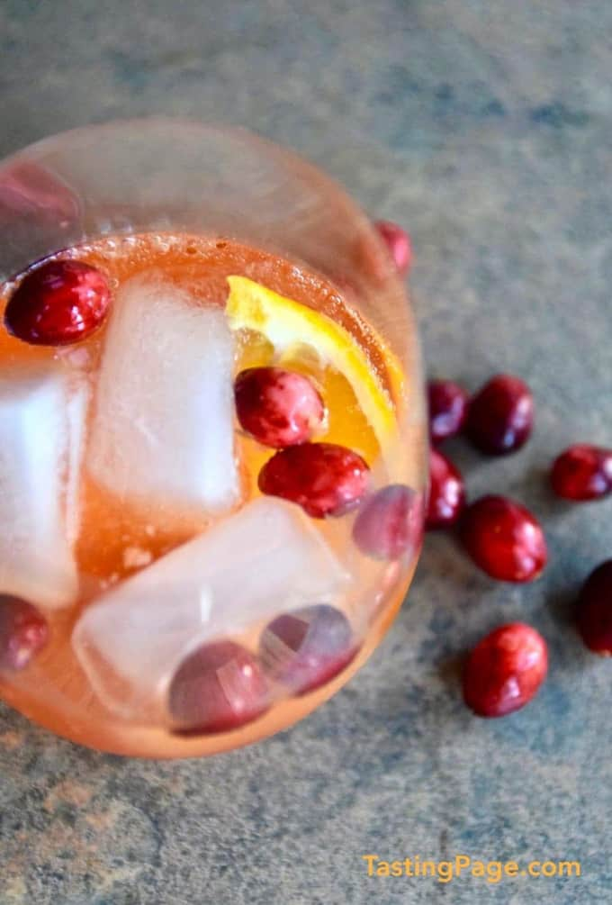 a glass of sparkling cranberry aperol spritz with ice cubes, orange slices, and fresh cranberries on a grey countertop