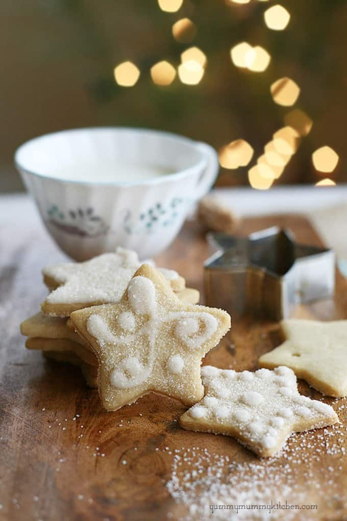 vegan sugar cookies on a wooden board with a cookie cutter and a mug in the background