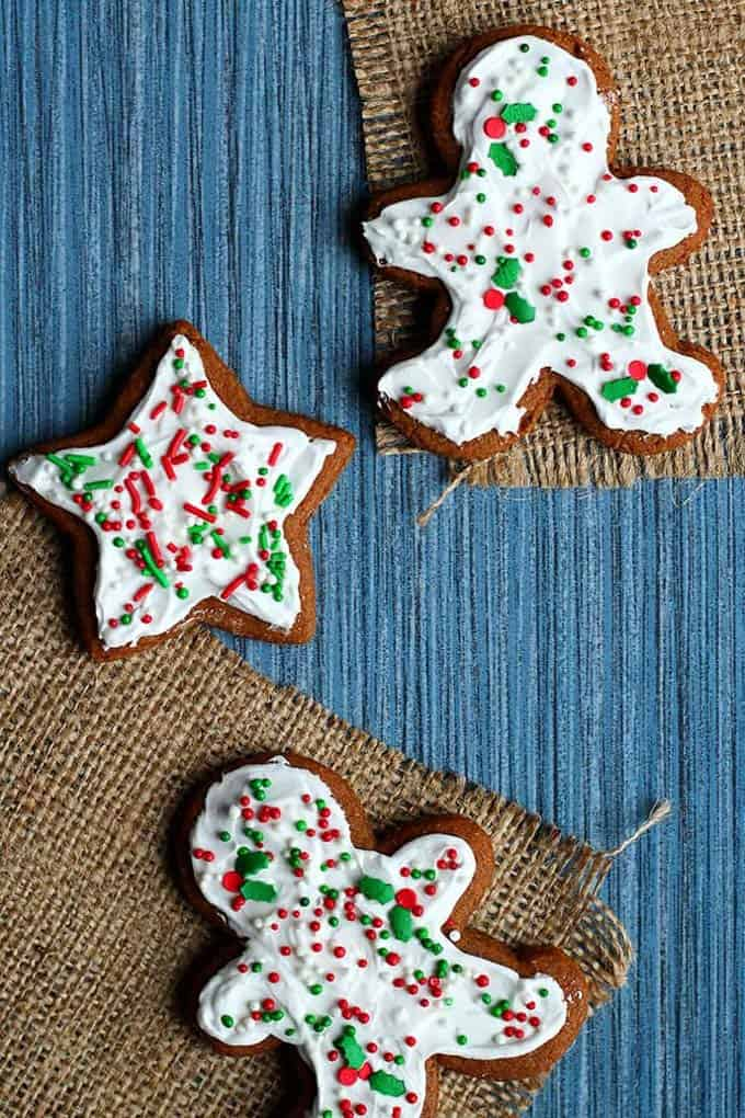two decorated vegan gingerbread man and a star-shaped gingerbread cookie on a blue wooden board