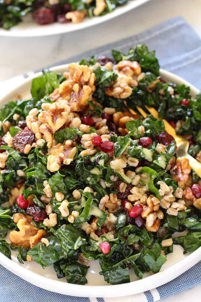 kale salad with pomegranate and walnuts on a white plate on a blue dish cloth