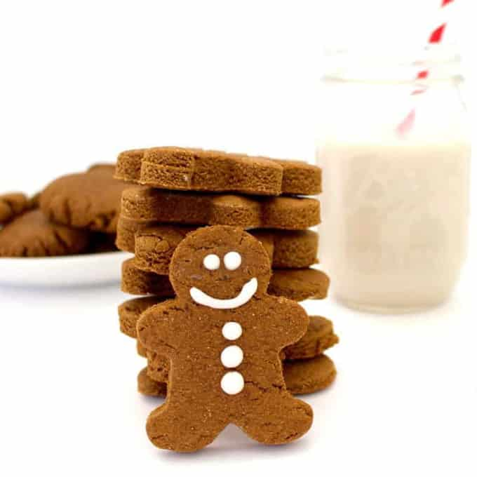 a stack of vegan gingerbread man with a glass of milk with a red straw in the background
