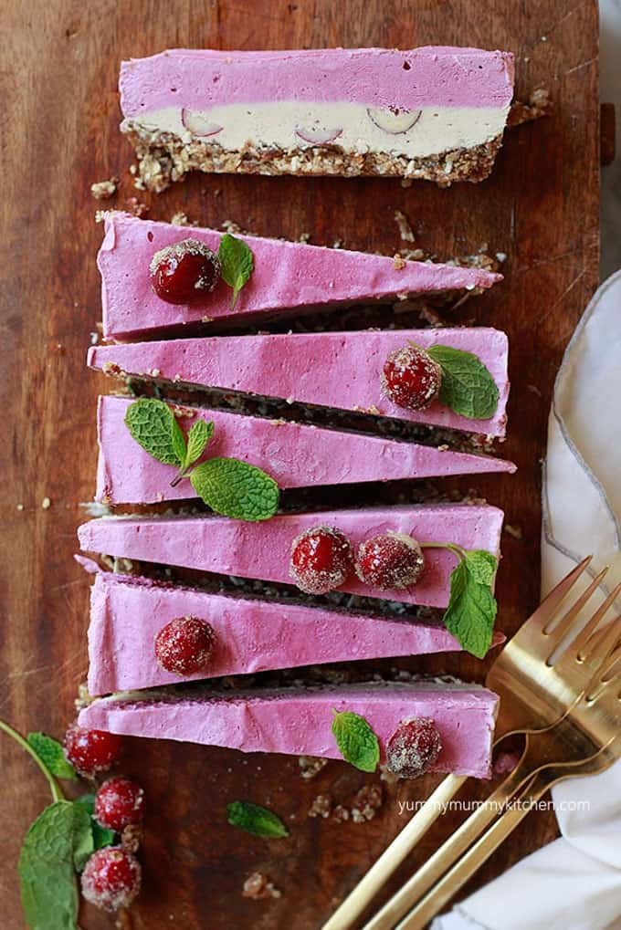seven slices of cranberry no bake cheesecake on a wooden board with three forks and mint leaves on the side