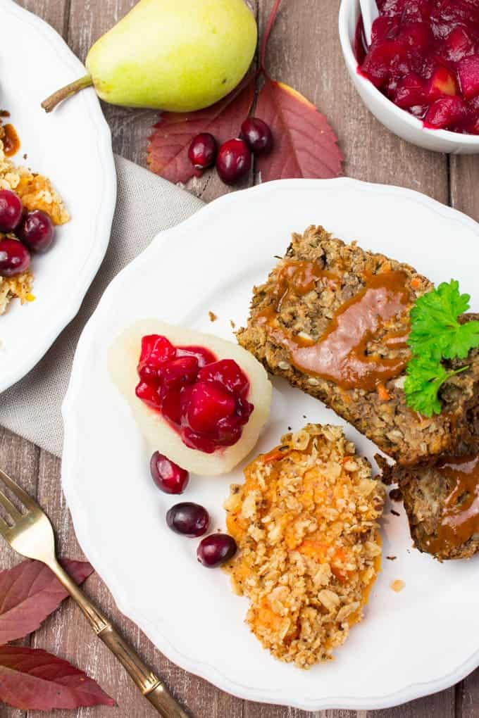 two slices of lentil loaf with vegan gravy and mashed sweet potato and cranberry sauce on a white plate on a wooden board with a fork and a small bowl of cranberry sauce on the side