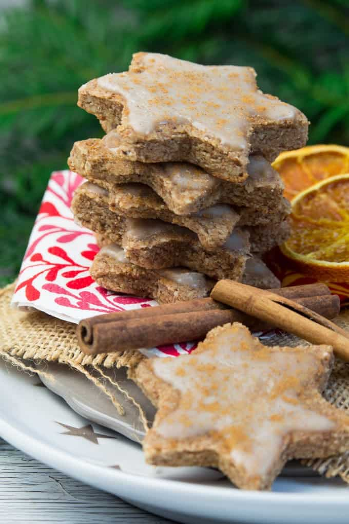 a stack of vegan star-shaped orange cinnamon cookies on a white plate with cinnamon sticks and dried orange slices on the side