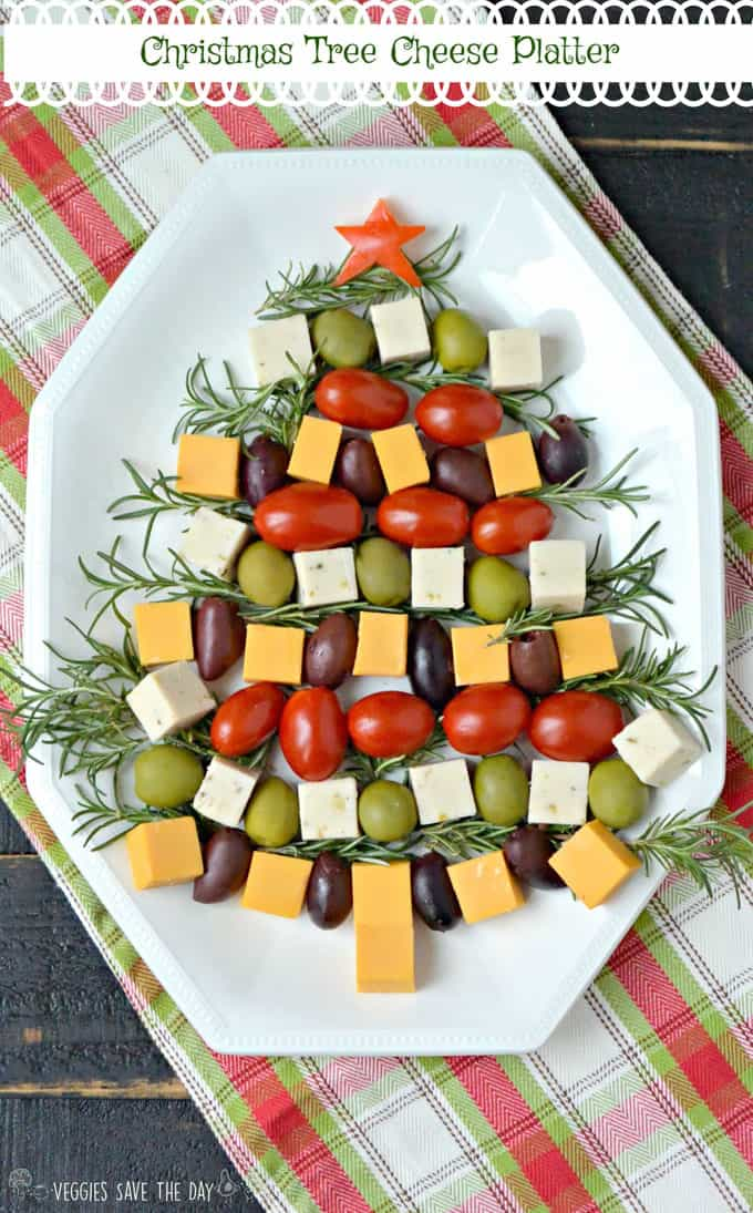 a vegan cheese platter with cherry tomatoes and olives formed to a Christmas tree on a white plate
