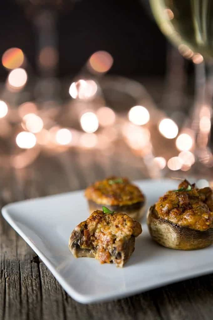 three vegan stuffed mushrooms on a white plate on a wooden board with lights in the background