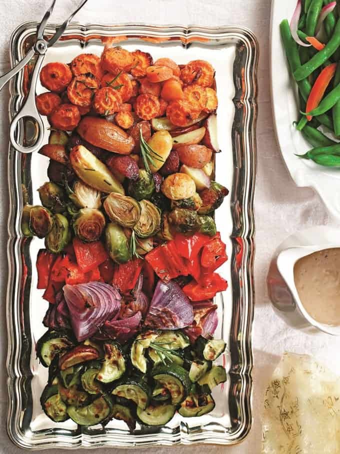 roasted carrots, Brussels sprouts, bell pepper, zucchini, and red onion on a serving plate with gravy and a plate of green beans on the side