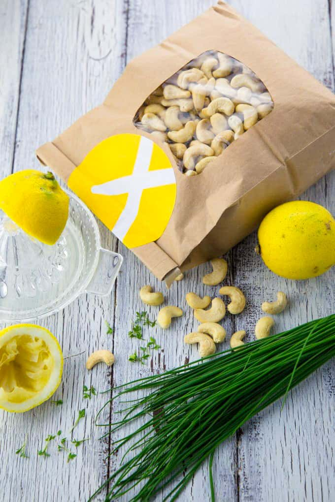 a paper bag of cashews, two lemons, a glass lemon squeezer, and chives on a white wooden board