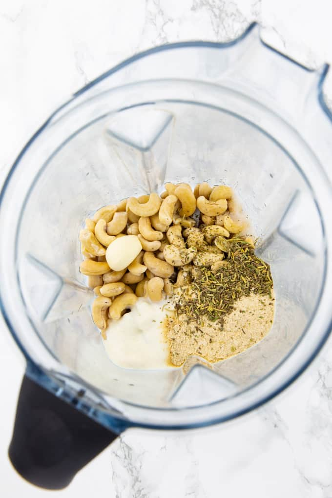 ingredients for vegan cream cheese in a blender before blending (cashews, soy yogurt, nutritional yeast, herbs, and garlic)